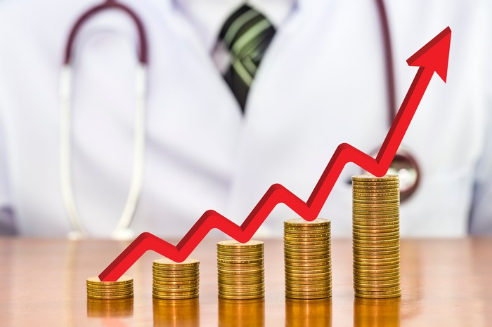 A red charting arrow rises on top of coin stacks of increasing height. A doctor sits in the background.