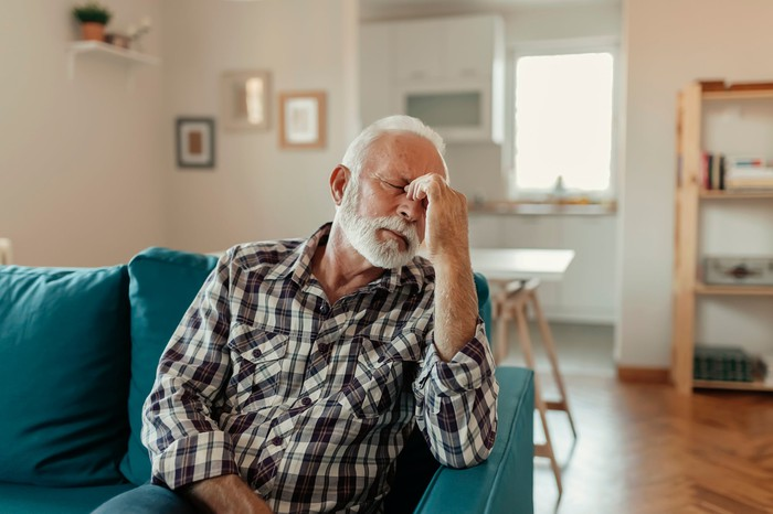 Older man sitting on a couch pinching the bridge of his nose.