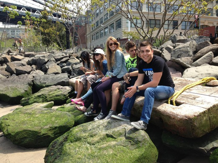 Six teens in American Eagle Outfitters clothing sit on a cluster of large rocks.