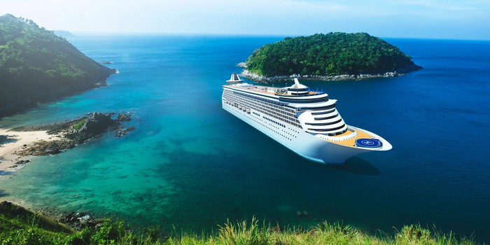 Cruise ship just off the coast, with a beach nearby and a wooded island.