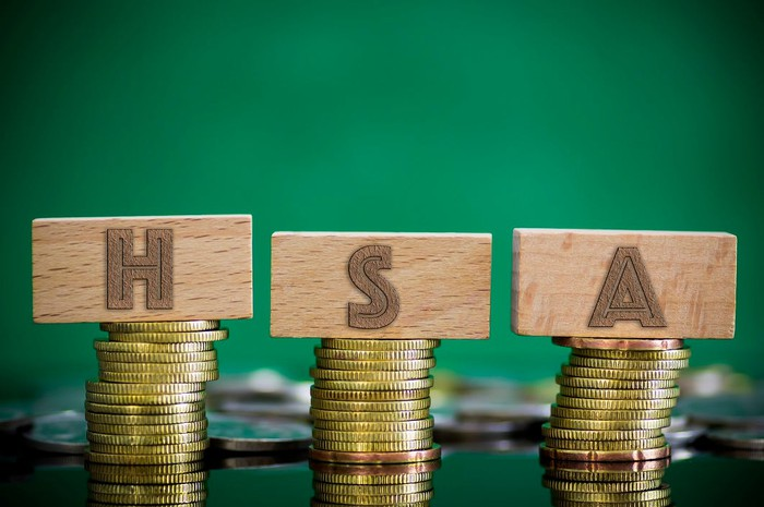 Piles of coins with letter blocks on top reading HSA.