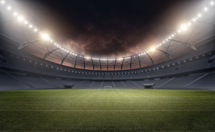empty football stadium at night under the lights