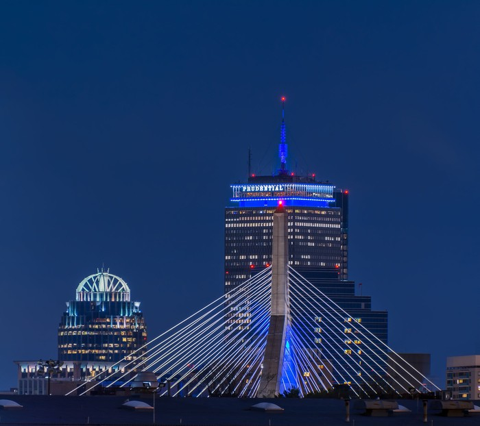 The Prudential Building in Boston at night, with the Zakim Bridge in the foreground.
