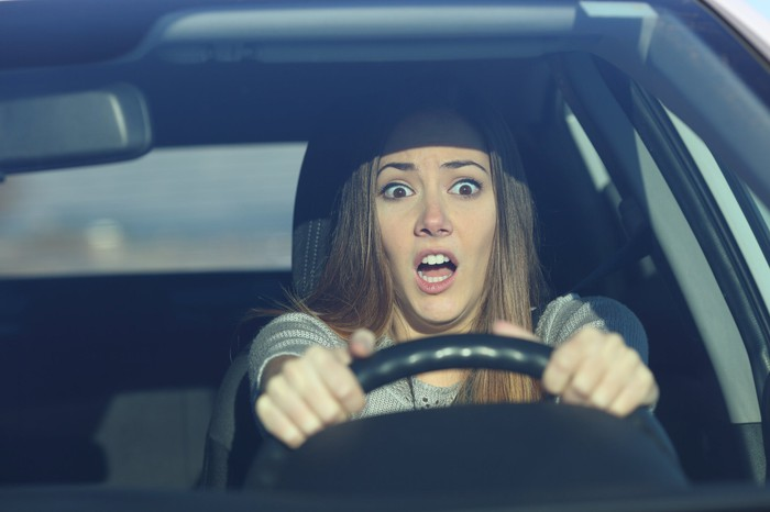 A surprised young woman driving a car.