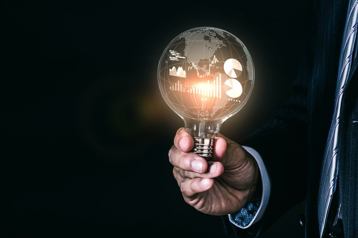A person holding a light bulb with a globe and charts and graphs inside.