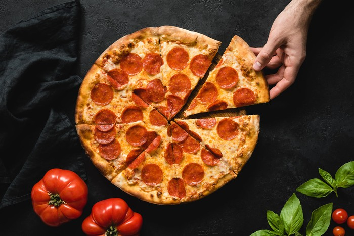 A hand grabs one piece of pepperoni pizza from a platter with 8 slices.