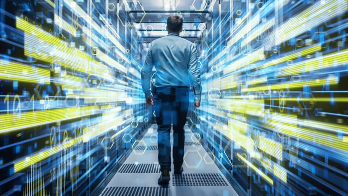 An IT professional walks into a data center with a visual overlay of charts and numbers.