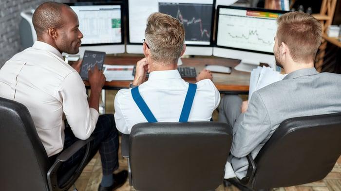 Three people gather around computers displaying stock charts.