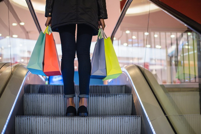 A lady holding four bags as she rides up an escalator at a mall.
