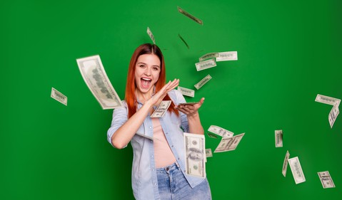 Excited woman scattering $100 bills