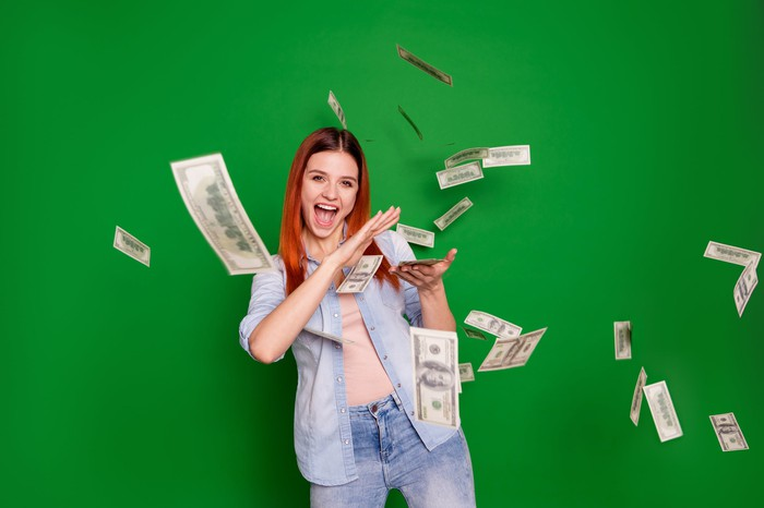 Excited woman scattering hundred dollar bills.