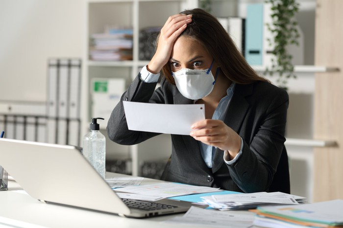 masked woman sitting at her laptop staring in disbelief at paper