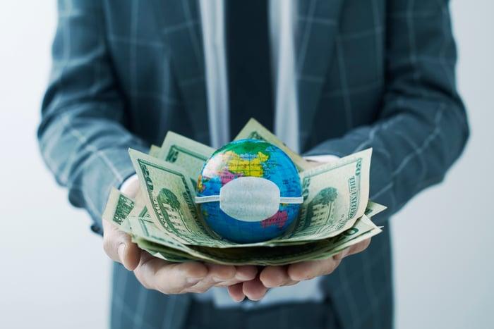 man holding money with masked globe