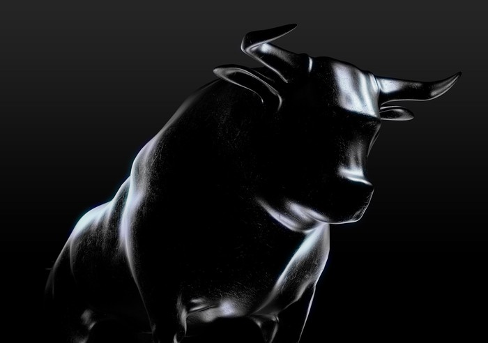 A sculpted metallic casting of a bull with a dark background.