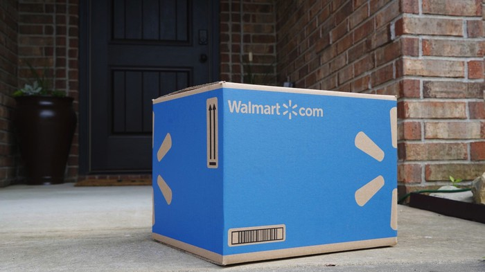 A blue Walmart shipment box sitting in front of a house.