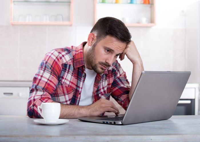 Man with sad expression looks at a laptop