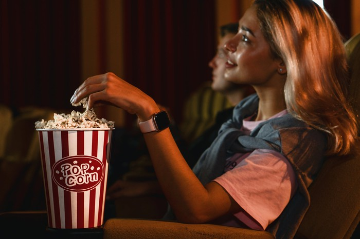 A woman and man watch a movie and eat popcorn in a movie theater.