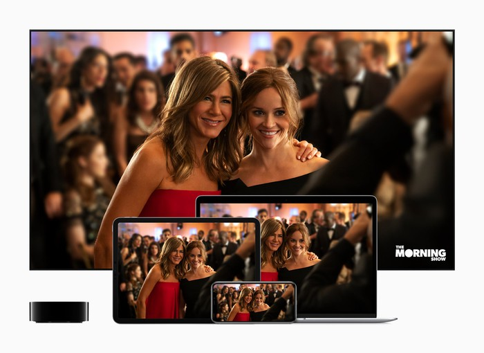 Jennifer Aniston with her arm around Reese Witherspoon in a scene from The Morning Show, as seen on multiple Apple devices