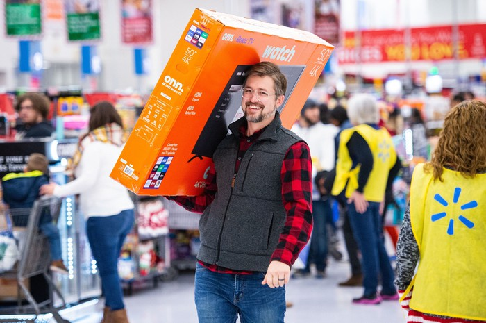 A Walmart customer carries a large package in the store.
