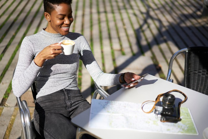 Young woman smiling at phone as she drinks coffee.