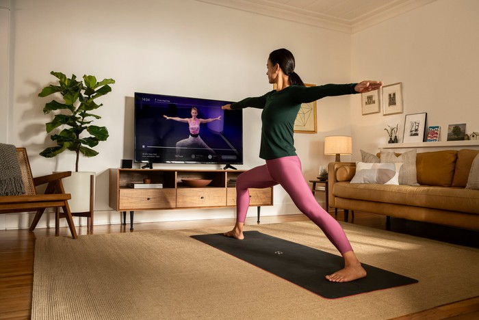 A woman doing yoga during an online Peloton fitness class projected on TV.