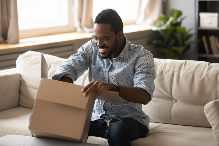 Smiling man opening package.