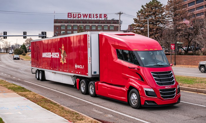 A red Nikola electric semi, shown hauling an Anheuser-Busch trailer.