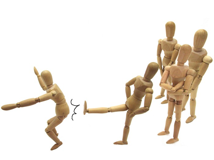 A group of poseable, wooden drawing figures kicking one member out