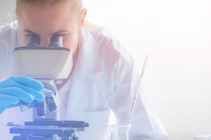 Scientist looking through a microscope in lab.