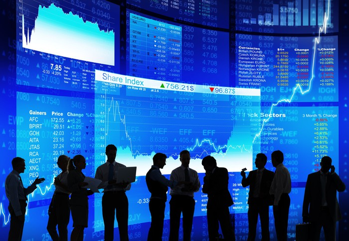 Numerous people in silhouette having a discussion with stock market tickers in the background.