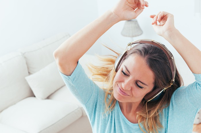 A girl wearing headphones while smiling and dancing.