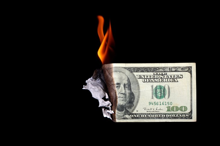 $100 bill on fire.