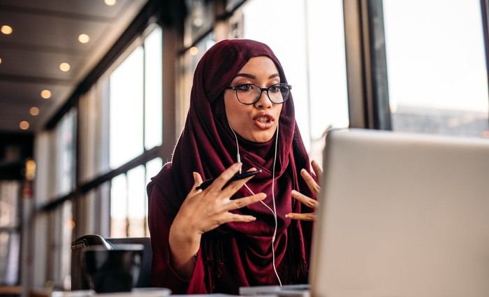 A woman talking and gesturing in front of her laptop.