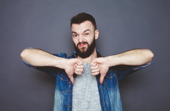 A bearded man expresses his dismay with two thumbs down.