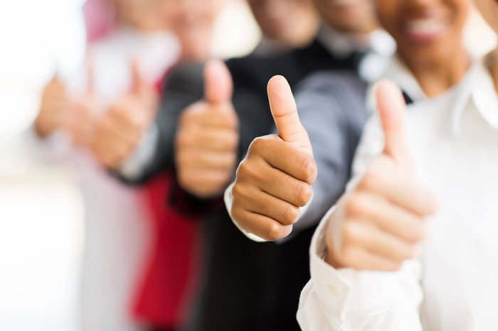 People standing in a line with their thumbs up