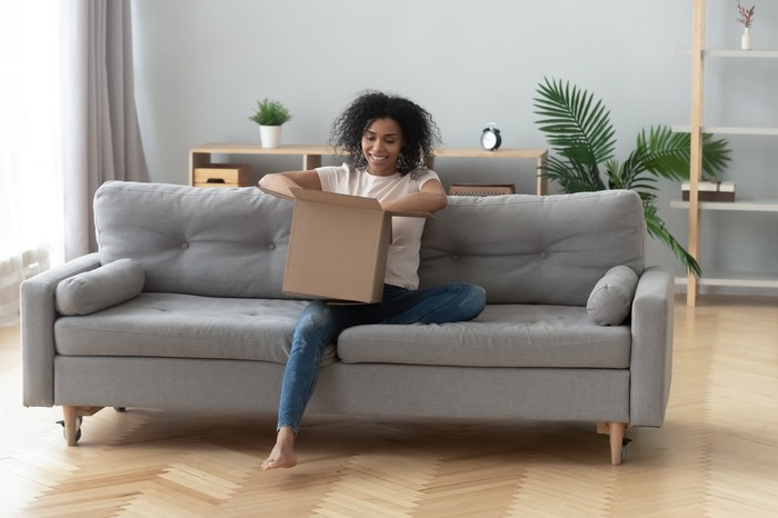 A woman sitting on a sofa and opening a box