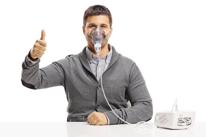 Man wearing a nebulizer mask and holding his thumb up