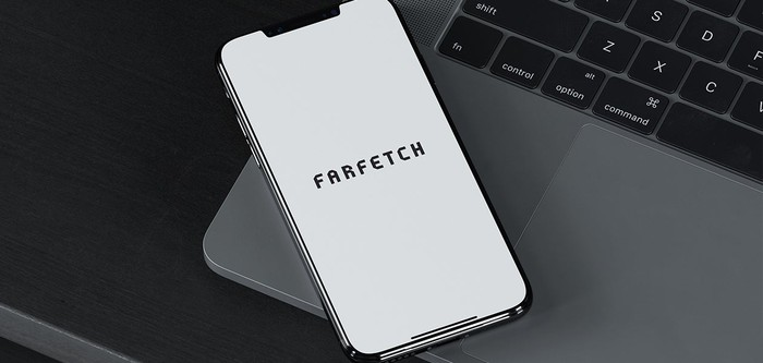 An iPhone with the Farfetch app open, resting on a laptop computer.