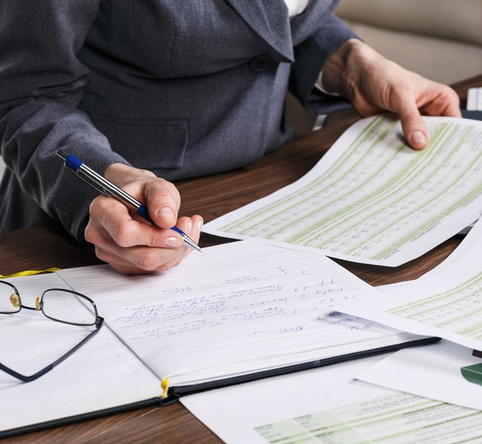 Close up of a woman holding financial documents and a pen reviewing papers at an office desk.