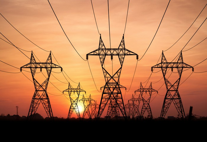 Electricity towers and power lines in front of a setting sun.