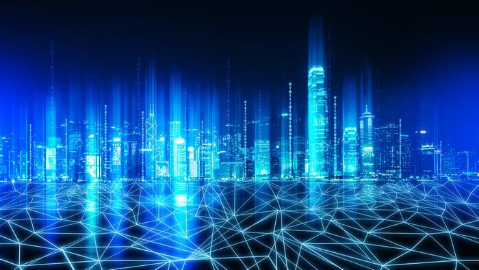 fiber lights up underneath a city skyline in luminescent blue.