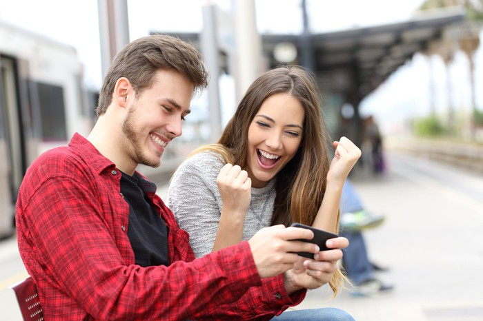 Two young people smile and laugh at a shared smartphone experience.