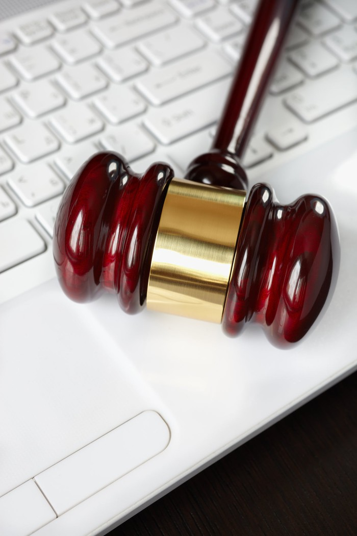 A judge's gavel rests on a laptop keyboard.