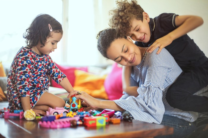 Kids climbing on mom while playing with toys