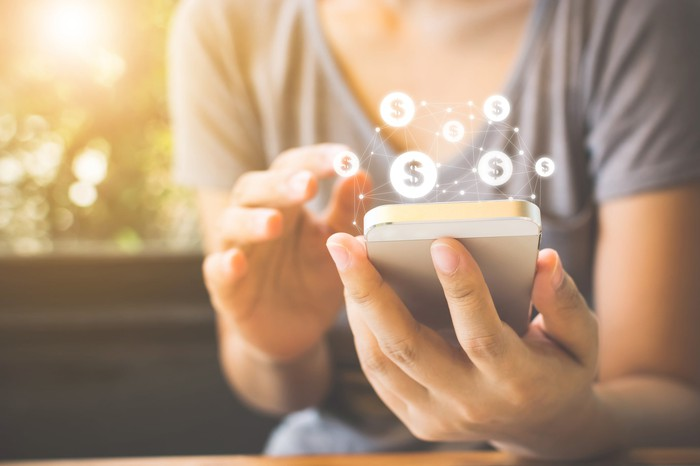 A woman holding a smartphone with financial symbols swirling above.