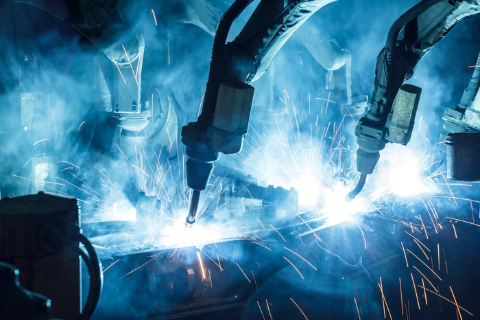 Robotic welding arms shooting off sparks.