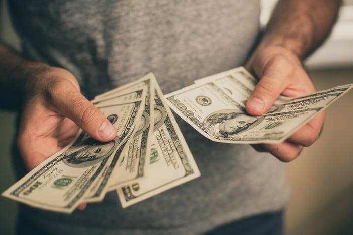 A man's hands hold a sheaf of $100 bills.