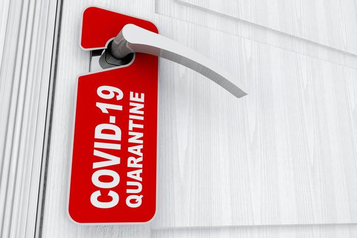 Do not disturb hotel room door hanger reads COVID-19 QUARANTINE