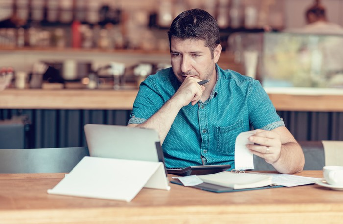 Man at table with tablet, notebook, and receipts