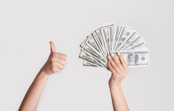 One hand holding a fan of $100 bills and another hand giving a thumbs-up